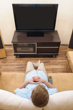 Mens die op bank ligt die op TV let. royalty-vrije stock afbeelding