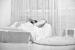 Mens die op bed leggen, wat betreft voorhoofd, wit gordijn op achtergrond Het concept van de hoofdpijn Kerel op pijnlijke gezicht stock afbeeldingen
