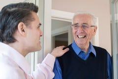 Mens die op Bejaarde Mannelijke Buur controleren stock foto