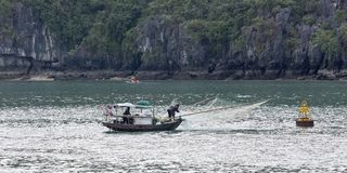 Mens die op bootboot bij Halong-Baai vissen royalty-vrije stock afbeelding