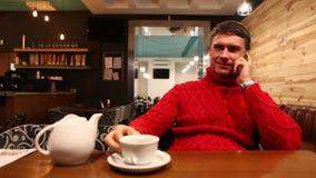Mens die op celtelefoon spreken in koffie stock videobeelden