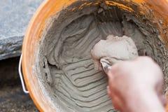 Mens die op cement legt dat in een emmer wordt gemengd Stock Foto's