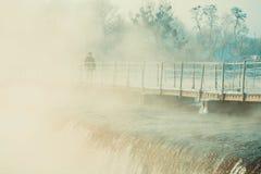 Mens die op de brug over de rivierwinter lopen Stock Foto's