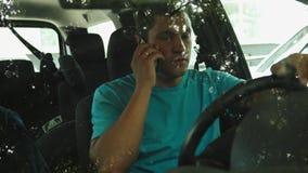Mens die op de mobiele telefoon in geparkeerde auto spreken stock footage