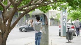 Mens die op de oude bazaar van Taza van de straat openbare telefoon spreken stock video