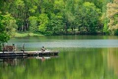 Mens die op de pijler tegen het meer liggen royalty-vrije stock afbeeldingen