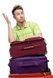 Mens die op de stapel van reiskoffers leunen Stock Afbeeldingen