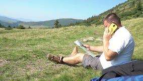 Mens die op de telefoon in bergen spreken stock footage