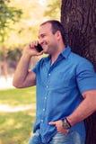 Mens die op de telefoon in een park glimlachen Stock Afbeeldingen