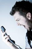 Mens die op de telefoon schreeuwt Stock Foto's