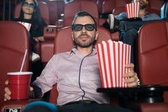 Mens die op een 3d film met wat popcorn letten Royalty-vrije Stock Foto