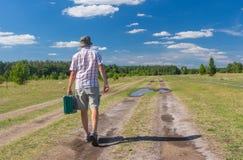Mens die op een de zomerlandweg lopen met groene koffer stock foto