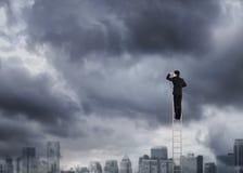 Mens die op een ladder over stad het vooruitzien beklimmen stock fotografie