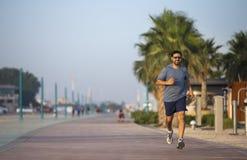 Mens die op een renbaan dichtbij strand lopen Stock Foto's