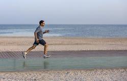 Mens die op een renbaan dichtbij strand lopen Stock Afbeeldingen