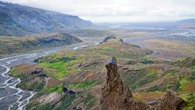 Mens die op een richel die van een berg situeren, van de mooie meningsvallei in Thorsmork genieten stock fotografie