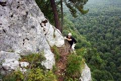 Mens die op een rots beklimmen Stock Afbeeldingen