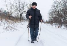 Mens die op een sneeuwweg lopen die houten stok 2 gebruiken royalty-vrije stock foto's