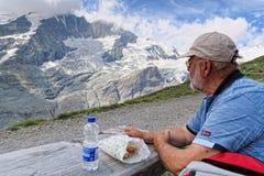 Mens die op een strand rusten en ontbijt eten die in grossglo wandelen Royalty-vrije Stock Afbeeldingen