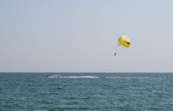 Mens die op een valscherm erachter boven het overzees vliegen Stock Afbeelding