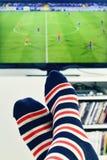 Mens die op een voetbalgelijke in TV letten stock foto's