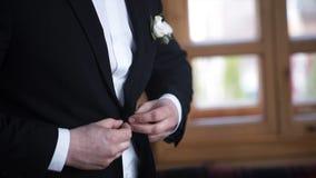 Mens die op een zwart jasje dichtknopen Huwelijksdetails - het elegante bruidegom geklede kostuum van de huwelijkssmoking wacht o stock afbeelding