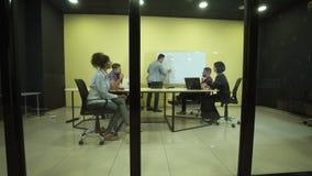 Mens die op flipchart op commerciële vergadering schrijven stock video