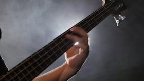 Mens die op gitaar een rotsoverleg spelen Bass Guitar-close-up stock videobeelden