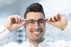 Mens die op glazen in optische opslag proberen terwijl gelukkig glimlachen royalty-vrije stock afbeelding