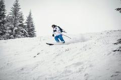 Mens die op helling ski?en Stock Foto's