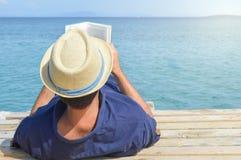 Mens die op het dok liggen en een boek lezen stock afbeeldingen