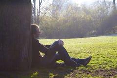 Mens die op het groene gras rust stock foto