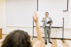 Mens die op het meisje op een klaslokaalachtergrond richten Student die hand voor een antwoord opheffen Het concept van het onder royalty-vrije stock foto's