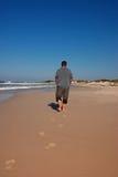 Mens die op het strand loopt stock foto
