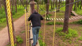 Mens die op kabels tussen bomen lopen stock footage