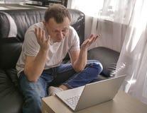 Mens die op laptop spreken terwijl het zitten thuis dichtbij het venster stock afbeeldingen