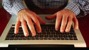 Mens die op laptop toetsenbord schrijven stock videobeelden