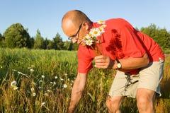 Mens die op middelbare leeftijd bloemen opneemt stock foto's
