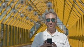 Mens die op middelbare leeftijd in grote spiegelglazen foto's op een smartphone bekijken stock video