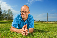 Mens die op middelbare leeftijd op een gras glimlacht Stock Foto