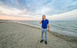 Mens die op mobiel op strand spreken Stock Afbeeldingen