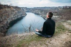 Mens die op rotsachtige klip met riviermening mediteren Royalty-vrije Stock Afbeeldingen