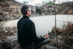 Mens die op rotsachtige klip met riviermening mediteren Stock Fotografie