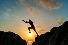Mens die op rotsen bij zonsopgang springen Royalty-vrije Stock Afbeelding