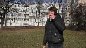 Mens die op slimme mobiele telefoon in park spreken Knappe kerels die gebruikend een slimme telefoon in het park spreken stock videobeelden