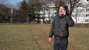 Mens die op slimme mobiele telefoon in park spreken Knappe kerels die gebruikend een slimme telefoon in het park spreken stock footage