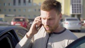 Mens die op smartphone spreken en in auto krijgen stock footage