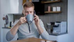 Mens die op smartphone tijdens ontbijt spreken stock video