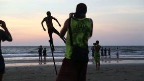 Mens die op steunpilaren op strand bij zonsondergang, met mensen het letten dansen op stock footage