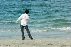 Mens die op strand rotsen werpt in overzees Royalty-vrije Stock Afbeelding